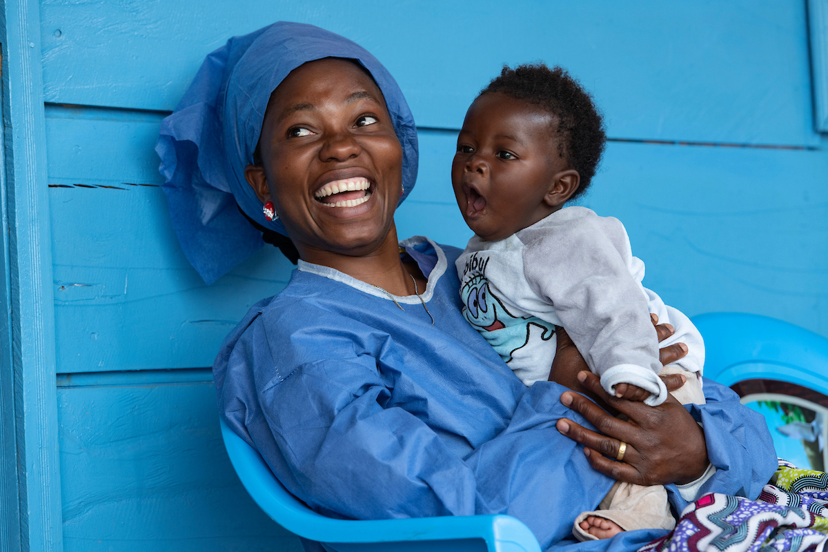 wilLullaby singer Joniste sits down while holding a baby in the Butembo Ebola crèche. She looks very happy while the baby yawns.