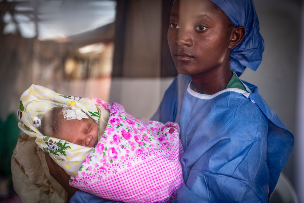 A lullaby singer holds an 8-day-old baby girl whose mother died of Ebola shortly after she was born. She is in intensive care and has a cannula placed in her head as it's the easiest place for them to find a vein due to dehydration.