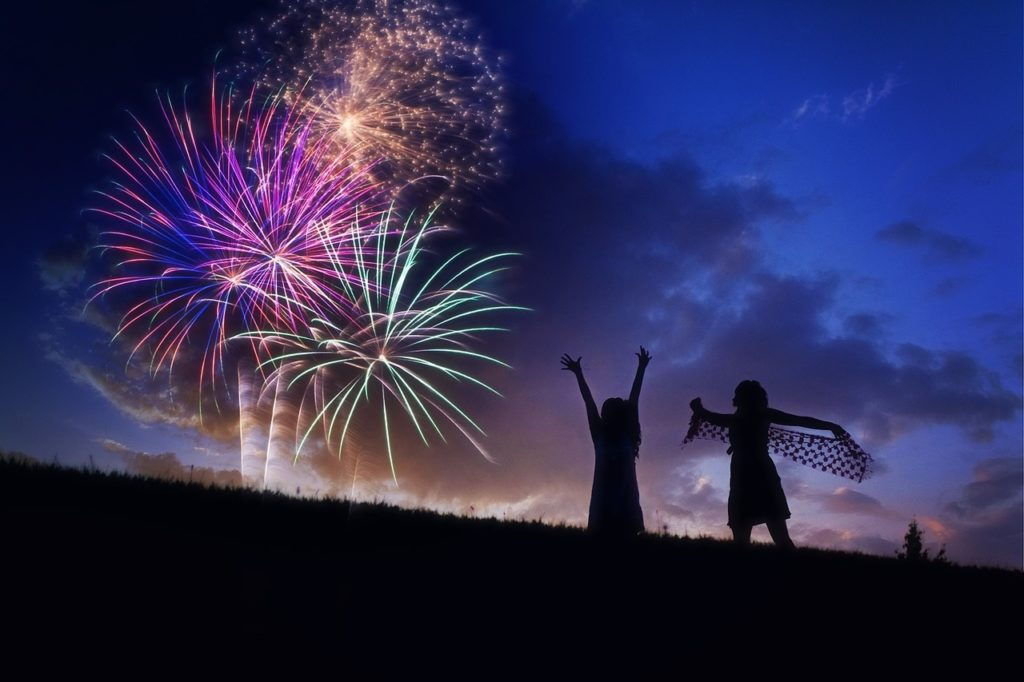 two girls standing on a hill with the night sky filled with fireworks