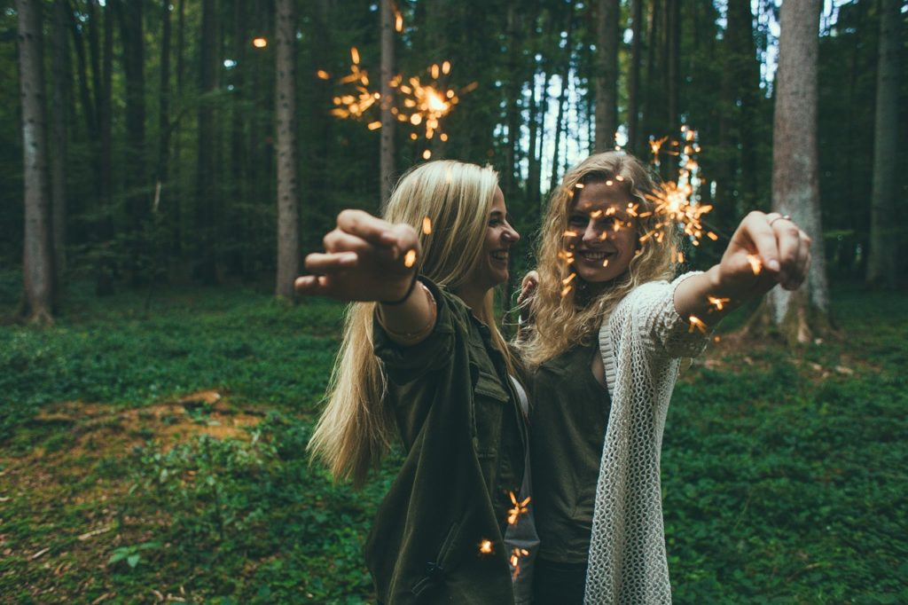 two girls standing in the woods holding sparklers